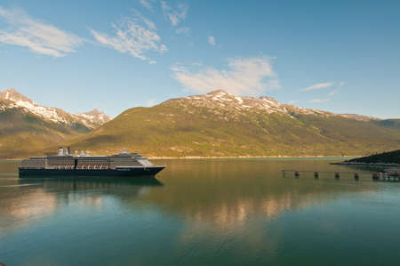 Cruise ship reaching and sailing into detination port with beautiful mountains. photo