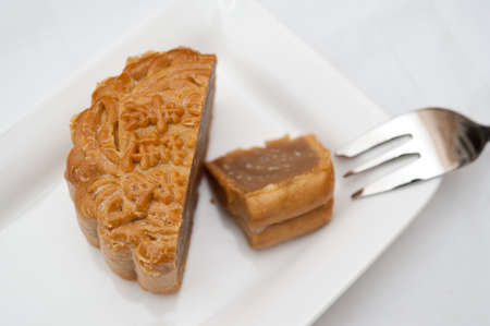 Delicious cut mooncake on white plate with dessert fork. photo