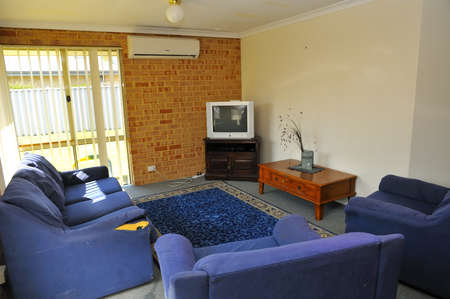 Interior of simple commong room with sofa and television.