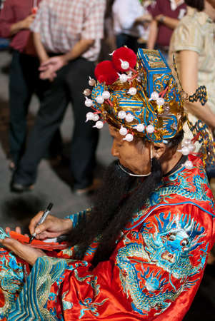 god of wealth chinese new year: Man dressed up as the Prosperity God writing well wishes on red slips of paper for good luck.