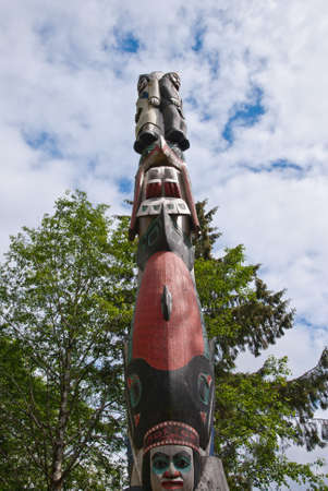 Majestic totem pole carved into interesting shapes, a symbol of aboriginal culture.