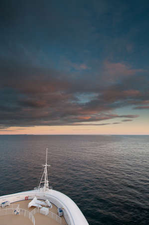 limitless: Cruise ship sailing in vast seas with low dark clouds at sunset.