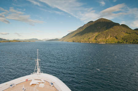 ship bow: View of sailing cruise ship bow approaching mountain in the open sea.