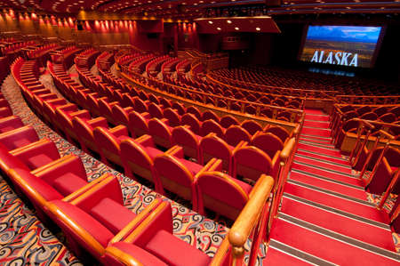 Empty auditorium with rows of red seats.