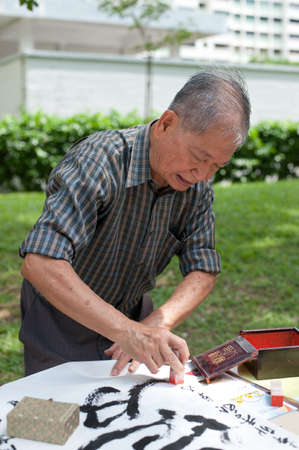 Calligrapher master Cai Zhuonan signing off on his work.