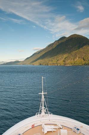View of sailing cruise ship bow approaching mountain. photo
