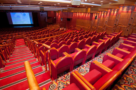 conference halls: Empty red seats in theater facing screen.