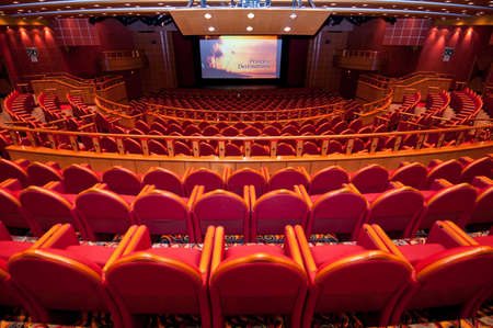 Back view of seats in auditorium with screen showing cruise Diamond Princesss promotional video.
