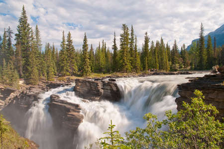 rockies: Majestic looking waterfalls with forest in background. Taken in the Rockies, Canada. Stock Photo