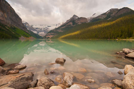 First rays of golden sunlight on the mountains at Lake Louise with peaceful reflections. photo