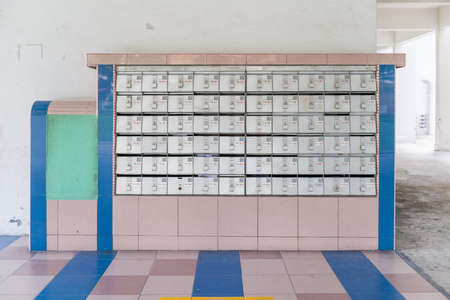 hdb: Rusty letter boxes or mail boxes with some containing letters in them. Communication, technology concepts.
