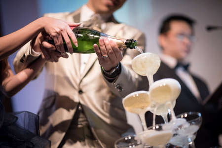 actual: Singapore, 09 Jan 2016: New wedding couple pouring champagne into glasses at banquet reception. Stock Photo