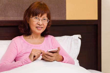 lifelong: Asian female senior lifelong learning concept through learning new mobile technology.