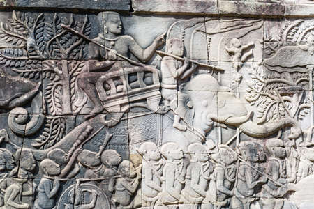 stone carvings: Stone carvings on walls depicting life of the past era at Angkor Thom. Stock Photo