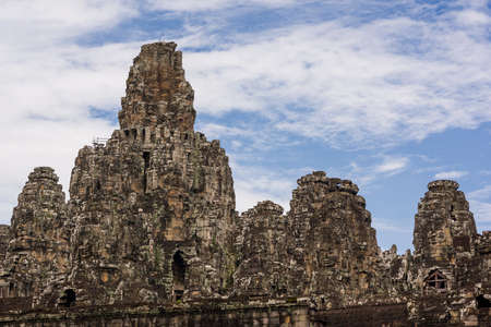 stone carvings: Majestic stone carvings and towers of Bayon Temple at Angkor Thom. Stock Photo