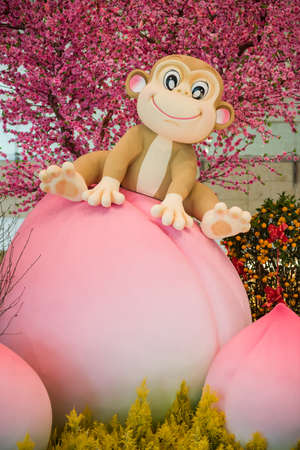 customs and celebrations: Singapore, 11 Feb 2016: Monkey mascot sitting on longevity peach as part of Chinese Lunar New Year decorations. Stock Photo