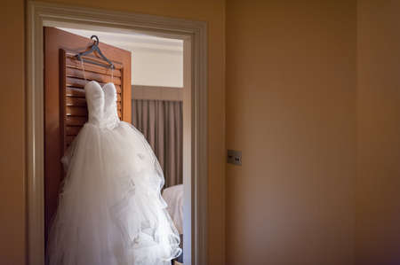 frilly: Pretty frilly wedding gown hanging on hotel room door.  This is the stunning Martini G dress that Sakura will be wearing. Absolutely love the frills!