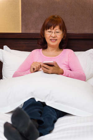 Asian female relaxing on bed learning new technology.