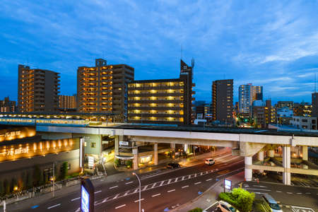 Kagawa, Japan - 24 July 2019: Eveing view of JR Ritusrin train station with housing apartments in background. Редакционное