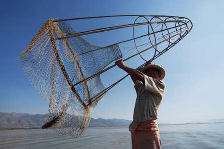 INLE LAKE, MYANMAR - FEBRUARY 16: Fisherman catches fish on February 16, 2011 on Inle Lake, Myanmar. The traditional fishing method is to use a long coop with net.