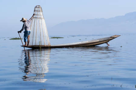 inle: INLE LAKE, MYANMAR - FEBRUARY 17: Fisherman catches fish for food on February 17, 2011 on Inle Lake, Myanmar. Intha people possess the feet-rowing style and the unique fishing equipment