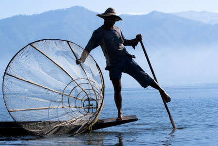 INLE LAKE, MYANMAR - FEBRUARY 17: Fisherman catches fish for food on February 17, 2011 on Inle Lake, Myanmar. Intha people possess the feet-rowing style and the unique fishing equipment Stock Photo - 16769266