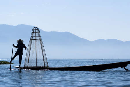Fisherman in Inle Lake makes a living by using a coop-like trap with net to catch fish Stock Photo - 16769448