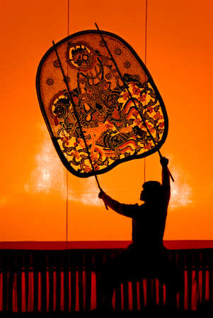 RATCHBURI, THAILAND - APRIL 13: Large Shadow Play is performed at Wat Khanon on April 13, 2011. The ancient performing art involves manipulating puppets of cowhide in front of a backlit screen with musical and narrative accompaniment