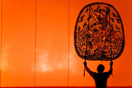 shadow puppets: RATCHBURI, THAILAND - APRIL 13: Large Shadow Play is performed at Wat Khanon on April 13, 2011. The ancient performing art involves manipulating puppets of cowhide in front of a backlit screen with musical and narrative accompaniment