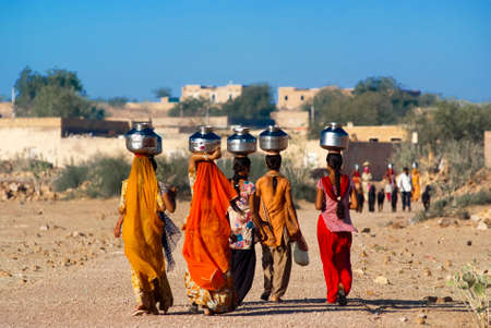 RAJASTHAN, INDIA – FEB 27  women lugging a water pot on their head on February 27, 2013 in Rajasthan, India  Due to the lack of piped water, poor tribals have to fetch water from its natural sources