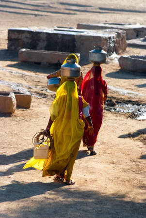lack of water: RAJASTHAN, INDIA – FEB 27  women lugging a water pot on their head on February 27, 2013 in Rajasthan, India  Due to the lack of piped water, poor tribals have to fetch water from its natural sources