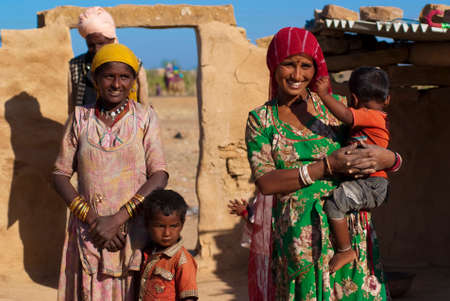 RAJASTHAN, INDIA – FEB 27  Rajasthani family in front of their mud hut on February 27, 2013 in Jaisalmer, India  There are many tribes in Rajasthan with the differences in costumes, jewellery etc