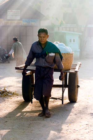 NYAUNG-U, MYANMAR-FEB 14  A local man pulls a rickshaw at the Nyaung-U market on Feb 14, 2011 in  Nyaung-U, Myanmar  It is a local market where people come from all over the area to sell and buy products