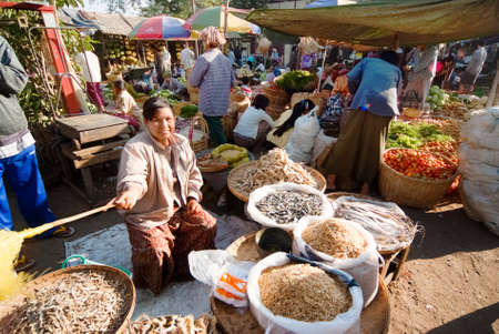NYAUNG-U, MYANMAR - FEBRUARY 14  Unidentified woman sells dried fish on February 14, 2011 at the Nyaung-U market, Myanmar  Nyaung-U is the primary gateway to the City of Bagan
