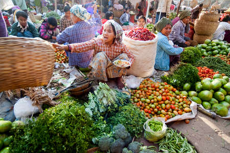 NYAUNG-U,MYANMAR-FEBRUARY 14  Unidentified girl sets up vegetable stall on February 14, 2011 at Nyaung-U market,Myanmar  It is a local market where people come from all over the area to sell products