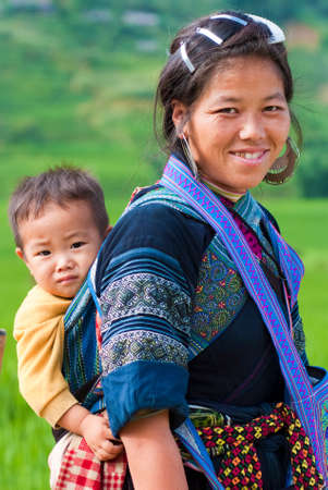 scarves: SAPA, VIETNAM – JULY 6: Hmong woman carries her child on the back on July 6 2009 in Sapa, Vietnam.  Hmong women are known for their indigo-dyed costumes and wrap long scarves around their legs. Editorial