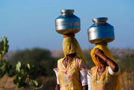 piped: RAJASTHAN, INDIA – FEB 27: women lugging a water pot on their head on February 27, 2013 in Rajasthan, India. Due to the lack of piped water, poor tribals have to fetch water from its natural sources.