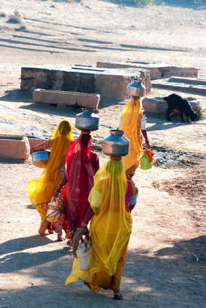 RAJASTHAN, INDIA – FEB 27: women lugging a water pot on their head on February 27, 2013 in Rajasthan, India. Due to the lack of piped water, poor tribals have to fetch water from its natural sources.