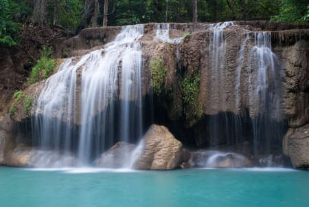 waterfall with sky: Waterfalls cascading off small cliffs into a turquoise pool Stock Photo