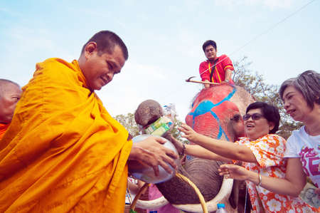 initiated: AYUTTHAYA, THAILAND - APR 13:  Thai people and elephant jointly give alms to monks during Songkran Festival on Apr 13, 2014 in Ayutthaya, Thailand. Initiated by Tourism Authority of Thailand, elephants take part in the festival.