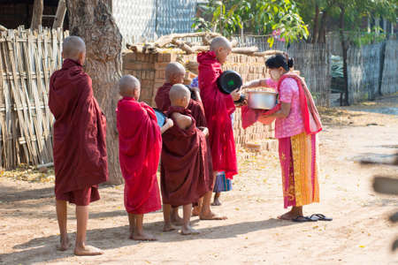 BAGAN, MYANMAR – MAR 2: A woman gives alms to novice monks on Mar 2, 2015 in Bagan, Myanmar. This behavior can be seen everyday in any village. Éditoriale