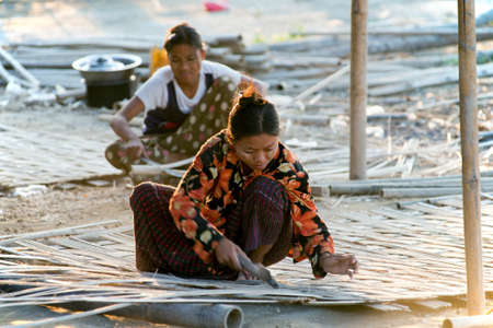MANDALAY, MYANMAR - MAR 6:  Local women are making bamboo panels on Mar 6, 2015 in Mandalay, Myanmar.  Bamboo logs are shredded into thin strips and cross-oriented and to be further used as wall, roof or mat.