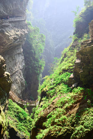 karst: Tourists walk through the Longshuixia Fissure Gorge along the path that winds itself into the fissure Stock Photo