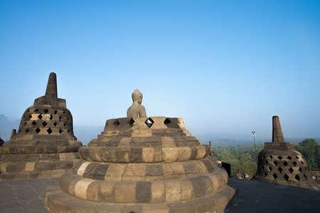 stupas: Buddha statue surrounded by stupas at Borobudur Stock Photo