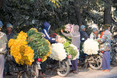 laden: MANDALAY, MYANMAR - FEB 2, 2016: Motorbikes laden with colorful flowers from Pyin Oo Lwin occupied the roadside to Mandalay on Feb 2, 2016.  This is where the sellers from cool hills and the buyers from the city meet to trade. Editorial