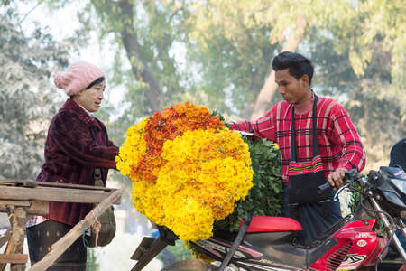 principally: MANDALAY, MYANMAR - FEB 2, 2016: Vibrant morning market on the roadside to Mandalay on Feb 2, 2016.  Flowers are principally used in Myanmar as offerings to Buddha, both in homes and temples.
