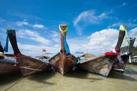 strikingly: KRABI, THAILAND – DEC 5, 2015: long-tailed boats for tourists are docked along the Railay Beach which is one of the most strikingly beautiful beaches in Thailand