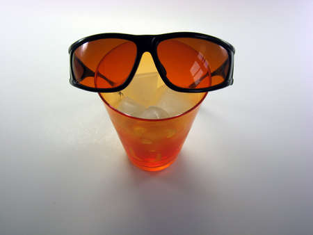 bright orange drinking glass with ice and blue blocker sunglasses  on a light background Stok Fotoğraf