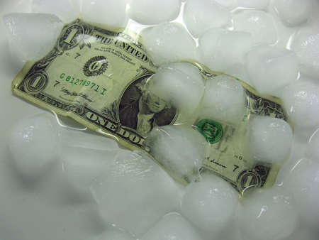 wet crumpled dollar bill under melting ice. The background is white. Lots of water. Stock Photo