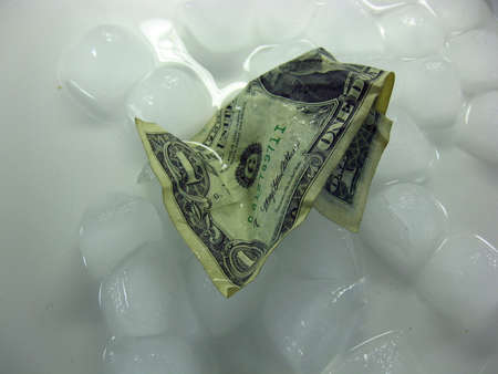 wet crumpled dollar bill on melting ice. The background is white. Lots of water. Фото со стока